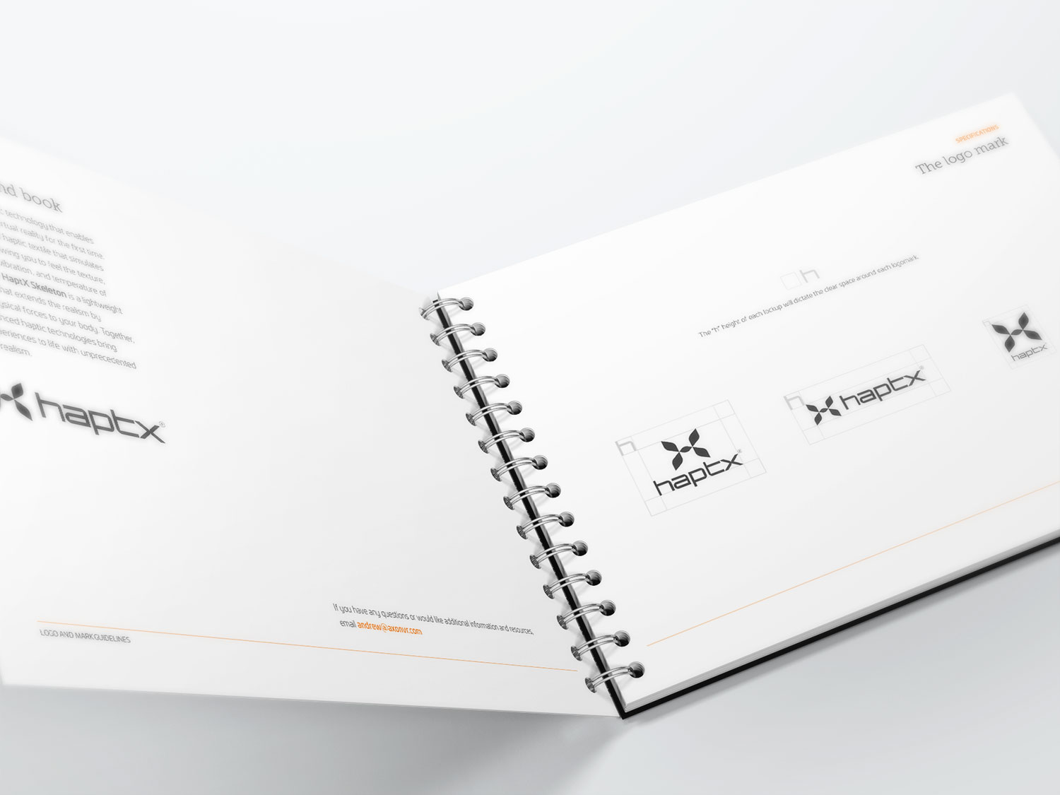 A HaptX book that has been opened to a page with the HaptX logo on it. The book is laying on a white table.